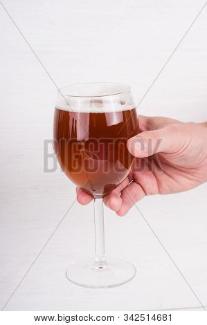 Homemade Craft Beer  In Wineglass In Male Hand On White Background.  Ale Or Lager From Pilsner Malt