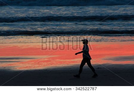 Beachgoer Walks The Edge Of Surf Near Crystal Pier During Red Sunset, San Diego