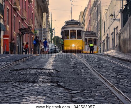 Travel Concept Of Lisbon's Famous Trams. Focusing On The Cobbled Streets With The Trams In The Foreg
