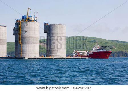 Ocean tug at the base of offshore oil drilling platform. Sea Japan. Russian coast.