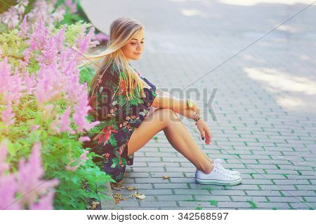 Portrait Of Beautiful Young Girl In Colorful Boho Vintage Dress Sitting Near Colorful Flowers. Roman