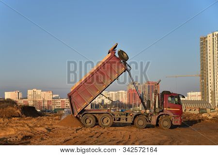 Red Dump Truck Dumps Its Load Of Sand And Soil On Construction Site For Road Construction Or For Fou