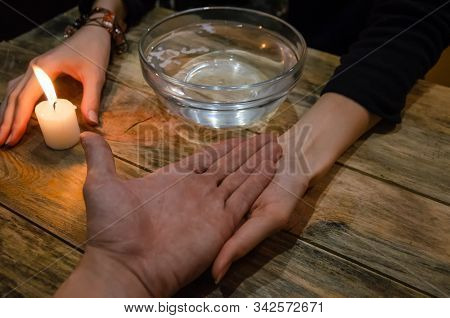 Divination With A Candle On The Water. Hand Of A Fortune Teller And The Hand Of A Man. Concept Of Ma