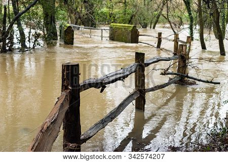 A Fence Leading To A Footbridge Becomes Part Of The River Mole In Brockham, Surrey, Uk, As Heavy Rai