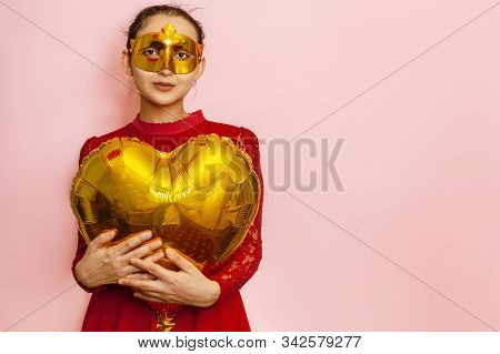 Woman Wearing Masquerade Mask And Holding Heart Shaped Air Balloon. Valentines Day, Birthday, Annive