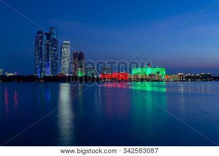 Abu Dhabi, Uae - November 29, 2019: Abu Dhabi Skyline With Emirates Palace And Etihad Towers Lit Up