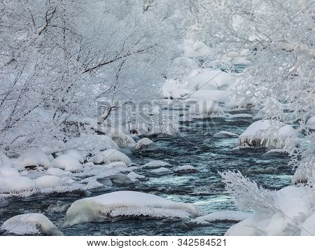 A Streaming Winter Creek, Snow And Ice, River Surrounded With Snow Covered Trees