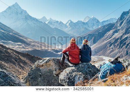 Couple Resting On The Everest Base Camp Trekking Route Near Dughla 4620m. Backpackers Left Backpacks