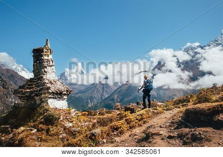 Young Hiker Backpacker Man With Trekking Poles Enjoying The Ama Dablam 6814m Peak Mountain During Ac