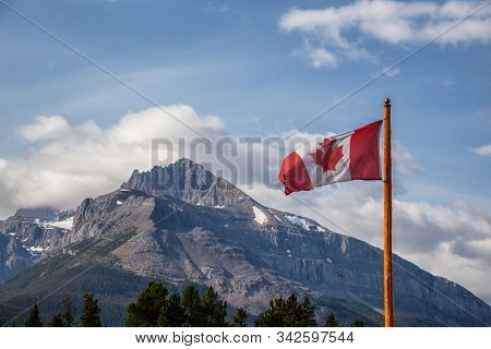 Canadian Flag With Rockie Mountains In The Background During A Sunny Summer Day. Taken In Banff Nati