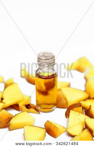 Close Up Shot Of Cut Raw Potato Along With Its Concentration In A Small Glass Bottle Isolated. Horiz