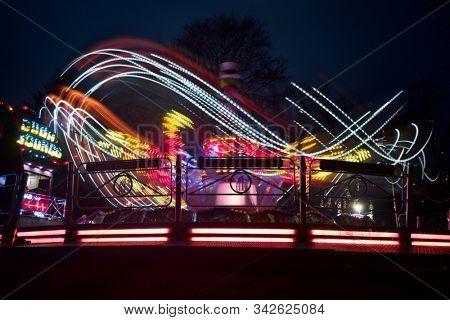 READING, UK - DECEMBER 27, 2019: Bright lights on a thrill ride at a funfair in Reading, Berkshire, UK.