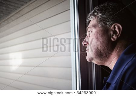 Middle aged man looking out the window, depression and loneliness. Shallow focus on man's nose, reflection in window