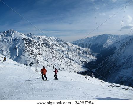 Skier Standing On A Slope. Girl In A Light Suit, The Helmet And Mask In Skiing Is To Ski. In The Bac