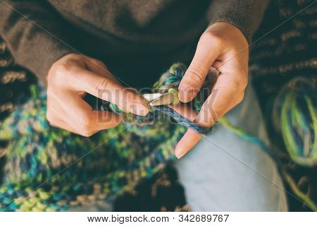 A Woman Knits From Thick Yarn. Handmade Clothes. The Girl Sits On The Couch And Goes In For Her Hobb