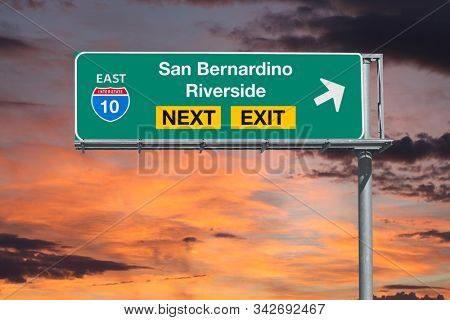 San Bernardino and Riverside California route 10 freeway next exit sign with sunset sky.