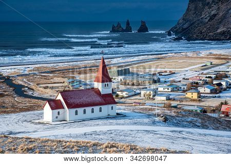 Icelandic Village Of Vik, Southeast Iceland With The Vik I Myrdal  Church At The Top Of The Hill Off