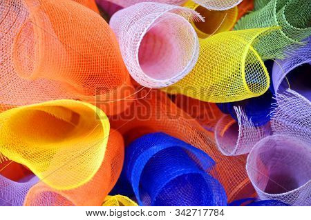 Colorful Rolls Of Craft Netting Lays In A Bunch.  Angle Shows End Of Curling Rolls.