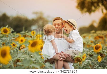 A Happy Family Walks In A Field Of Sunflowers. Young Handsome Dad With Two Children In A Sunflower F
