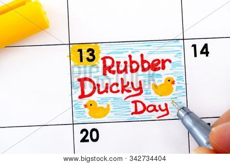 Woman Fingers With Pen Writing Reminder Rubber Ducky Day In Calendar. January 13.