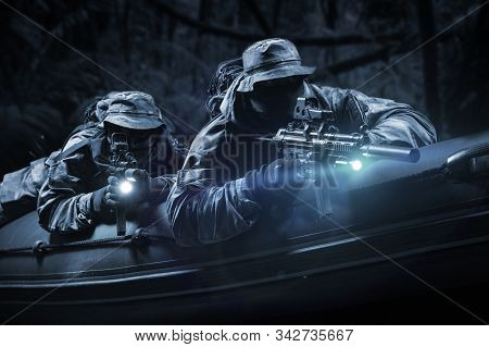 Two Fighters Of A Special Unit Move Through The Forest At Night. The Concept Of Special Operations,
