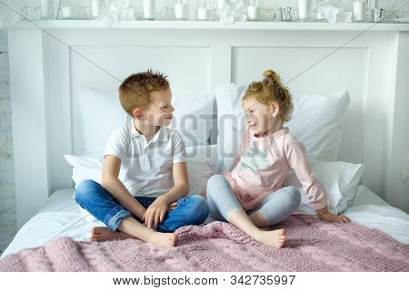 Brother And Sister Boy And Girl Play Together In Bedroom. Little Girl Look On Her Brother. Happy Chi