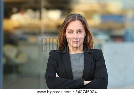 Front View Of A Confident Executive Looking At Camera Folding Arms In The Street Beside An Office