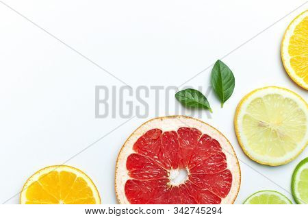 Flat Lay Composition With Slices Of Fresh Lemon Orange Grapefruit Lime Green Leaves On White Backgro
