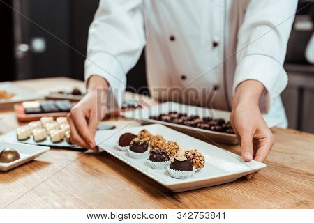 Cropped View Of Chocolatier Touching Plate With Sweet Fresh Chocolate Candies