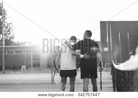 Father And Son Playing Tennis Outdoors.