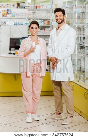 Customer With Jar Of Pills And Druggist Smiling At Camera With Pharmacy Showcase At Background