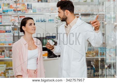 Druggist Holding Jar Of Pills And Pointing At Showcase To Customer