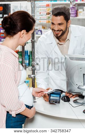 Pregnant Customer Paying With Credit Card And Smiling To Druggist At Counter