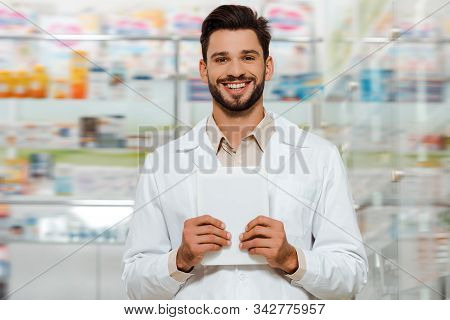 Druggist Holding Digital Tablet And Smiling At Camera In Apothecary