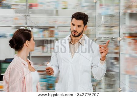Druggist With Pills Pointing At Medicaments In Showcase To Customer