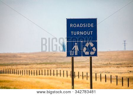 Information Road Blue Sign, Roadside Turnout With Tidy Man And Recycling Symbols On Canadian Rural C