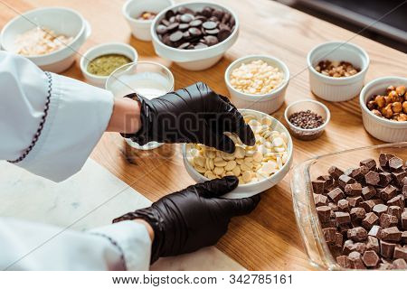 Cropped View Of Chocolatier In Black Latex Gloves Taking White Chocolate Chips Near Bowls