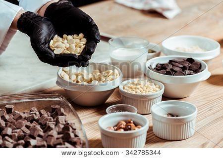 Selective Focus Of Chocolatier In Black Latex Gloves Holding White Chocolate Chips