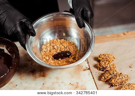 Cropped View Of Chocolatier In Black Latex Gloves Holding Bowl With Flakes Near Delicious Chocolate