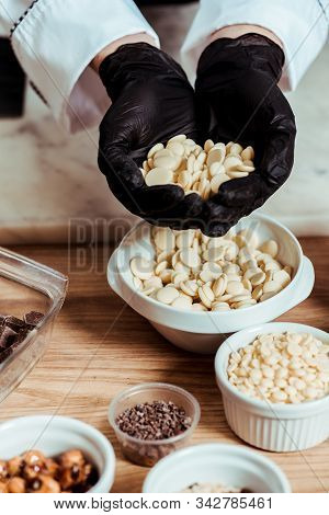 Cropped View Of Chocolatier In Black Latex Gloves Holding White Chocolate Chips