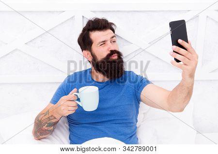 Selfie Kiss. Bearded Man Take Selfie In Bed. Hipster Smile To Selfie Camera In Mobile Phone. Enjoyin