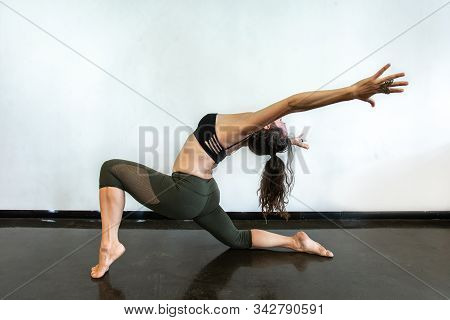A Side Profile Shot Of A Flexible Gymnast Performing An Intensive Vinyasa Flow Yoga Session, With Cu