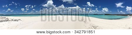 Panoramic Image Of White Sand And Turquoise Waters Underneath A Bright Blue Sky With White Puffy Clo