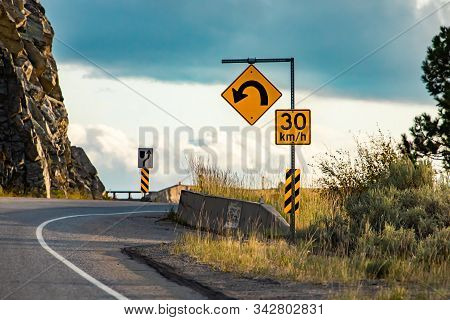 Yellow Warning Road Sign U-turn With 30 Km Per Hour Maximum Speed Posted Under Curve Warning Sign On
