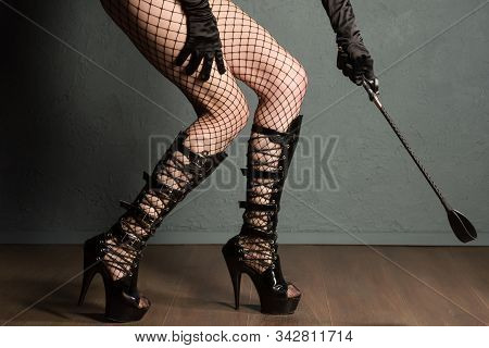 Adult Sex Games. Sexy Girl Legs In Fishnet And High Heels Fetish Boots With Whip Prepare For Punishm