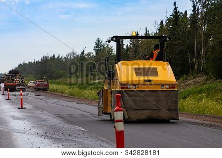 A Heavy Duty Road Roller Is Seen Compacting Asphalt Subsurface During Roadworks On A Major Freeway,