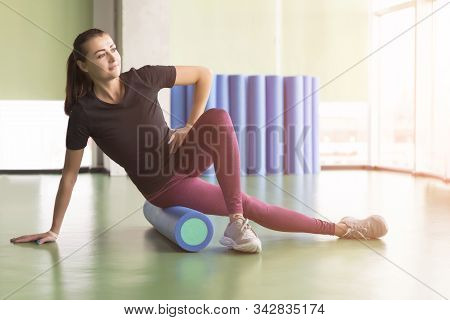 Attractive Female Doing Foam Roller Exercise And Posing In Modern Bright Fitness Center