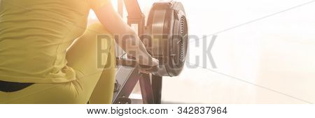 Back View Of Woman Uses A Rowing Machine