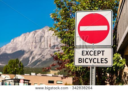 Selective Focus On Do Not Enter Road Sign With Except Bicycles Sign, Against Buildings And Mountains