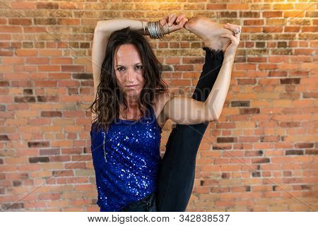 Stern Looking Woman As She Practices A Grueling Vinyasa Yoga Routine Inside A Gym Against An Orange